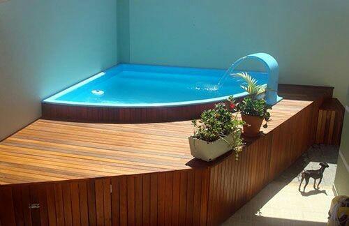 49 – Área de lazer com piscina em fibra de vidro de canto, deck