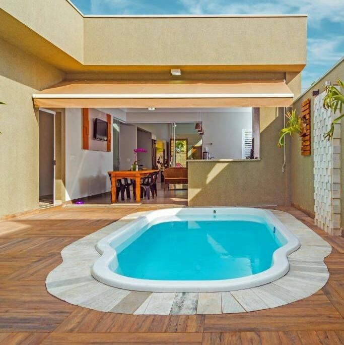 piscina em fibra de vidro, bordas de mármore e piso em madeira