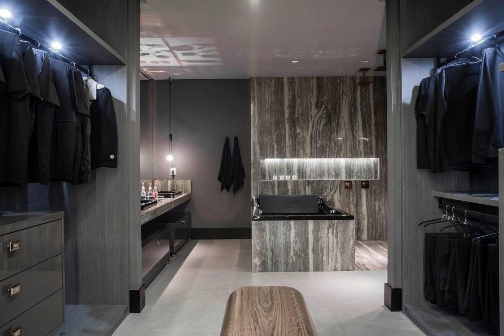 Suíte Master 35 –Neste projeto mais masculino o cinza e o preto predominam tanto no closet, quanto no banheiro que conta com uma banheira em estilo tradicional preta.