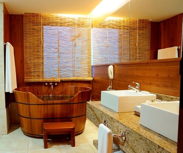 35. Banheiro em estilo rústico com banheira ofurô de imersão em madeira e pia dupla.