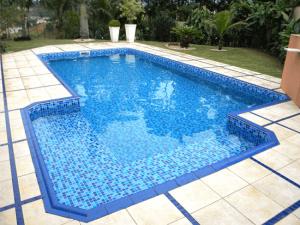 02-Piscina vinil geométrica com padrão pastilha azul e piso externo em pedra São Tomé e detalhe de rejuntes em azul