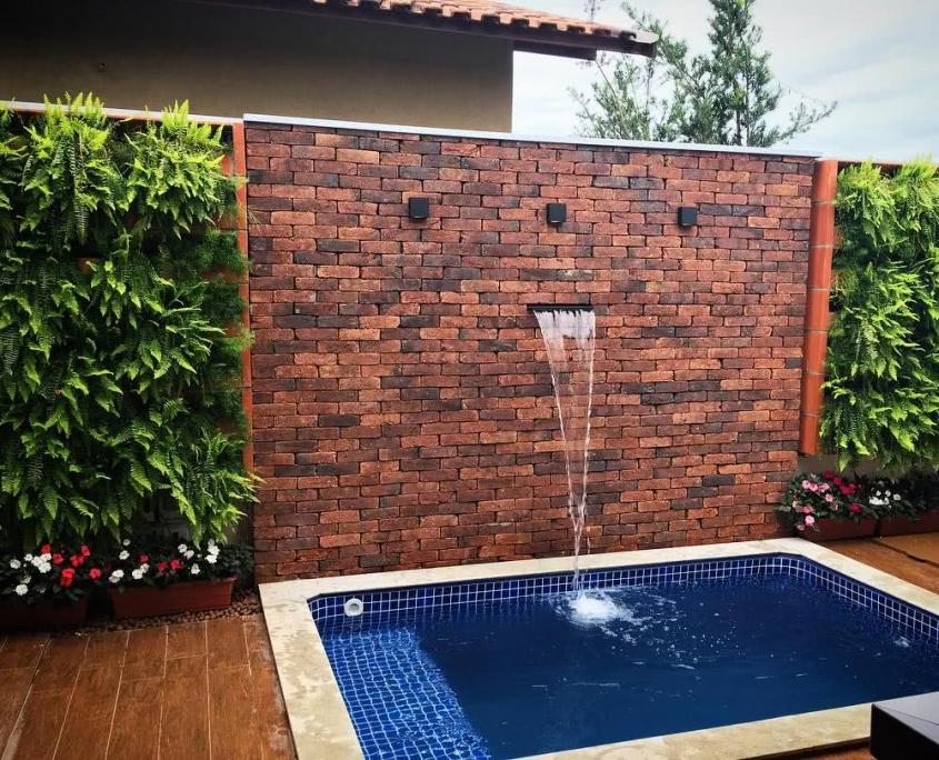 08-Piscina vinil pequena retangular padrão pastilha azul escura, muro de pedra com cascata com muro verde conjugado