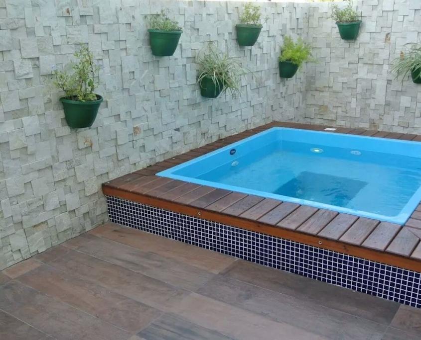 Piscina com dois níveis de profundidade em deck de madeira. O piso também de madeira contrasta com o muro de pedras brancas e jardim suspenso.