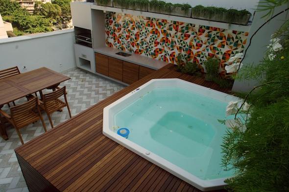 Piscina quadrada com hidro integrada em deck elevado de madeira. Este projeto conta ainda com uma área gourmet e churrasqueira.