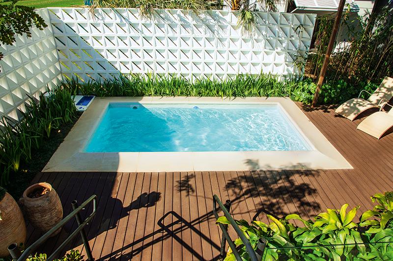Projeto da casa cor 2016, esta piscina quadrada pequena conta com deck de madeira e decoração com vasos de barro e espreguiçadeiras rústicas. O charme fica por conta do muro feito com estes lindos blocos decorativos vazados.