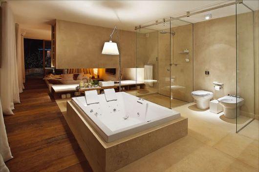Neste luxuoso banheiro integrado a suíte master o revestimento é a cerâmica, a banheira de hidromassagem de casal também é separada da ducha. A luminária dá um charme a mais evidencia a banheira.