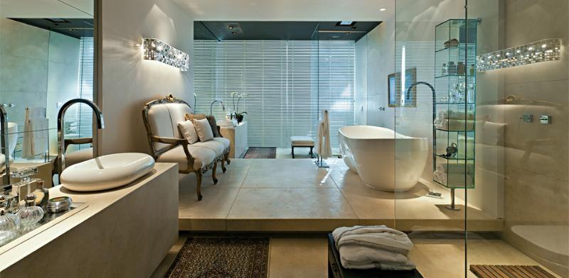 Neste banheiro a área de banho da banheira de imersão minimalista é separada das demais áreas e conta com um deck com um sofá no estilo Luís XV. Outros destaques desta proposta é a decoração com a luminária e a torneira de piso.