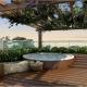 Jacuzzi redonda em deck de madeira embaixo de uma pérgola