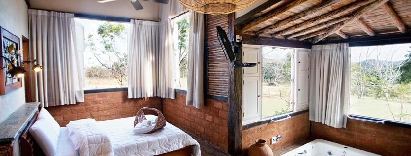 Quarto estilo rústico com banheira de hidro pequena embutida em piso de madeira.